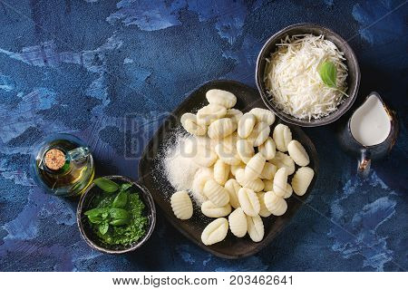 Raw uncooked potato gnocchi in black wooden plates with ingredients. Flour, grated parmesan cheese, pesto sauce, jug of cream, olive oil over dark blue concrete background. Top view. Home cooking.