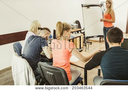 Learning language - English concept. Female teacher tutor near whiteboard screen giving lesson students making notes. Studies course