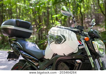 Picture of a motorcycle parked on a country road in a forest