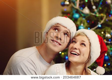 young couple celebrating Christmas at home. man and woman in santa hat. New Year and xmas people