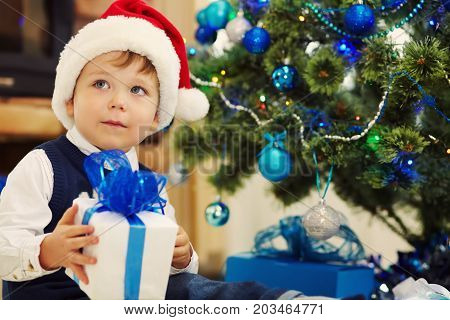 Cute little boy in santa hat holding a gift near Christmas tree. child with present. xmas kid