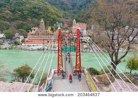 Rishikesh, India - March 8, 2017: People Crossing The Ganges River On The Suspension Footbridge At R