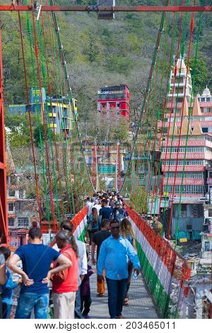 Rishikesh, India - March 10, 2017: People Crossing The Ganges River On The Suspension Footbridge At