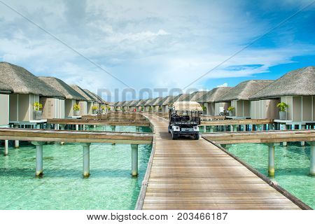 South Atoll Dhidhoofinolhu Maldives - 8 June 2017: Electric buggy golf сar for carriage of baggage on a wooden bridge near the over-water villas Maldives 8 June 2017