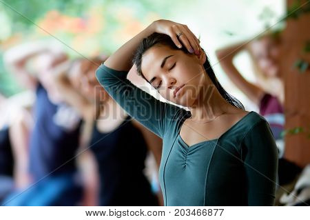 Moscow, Russia - May 2014. Yoga stretching neck. Public yoga classes. Exercise Stretching the neck. Girl with eyes closed stretches neck with his right hand.