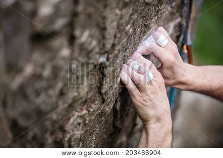Rock climber's hands gripping small hold on natural cliff closeup view