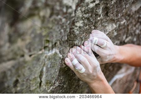 Closeup view of rock climber's hands gripping hold on natural cliff