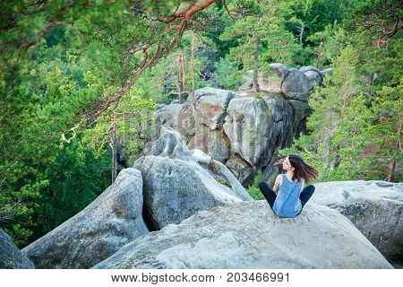 Young girl sitting on top of cliff against beautiful view of rocks and forest