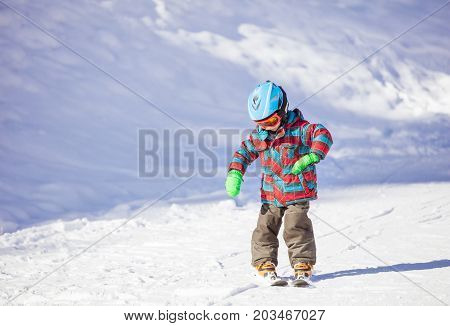 Little boy skiing downhill learning how to make turns