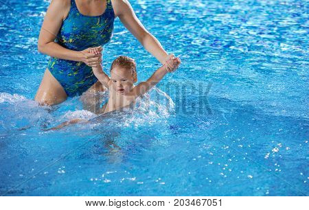 Young woman and little son in indoor swimming pool