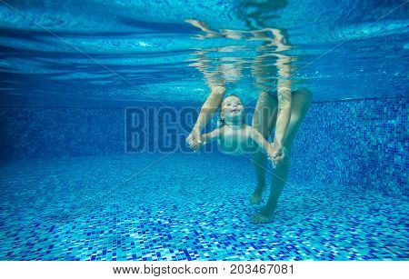 Little boy swimming underwater in indoor pool mother or instructor holding him by hands