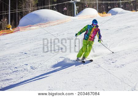 Young man skiing downhill on winter resort chairlifts in background