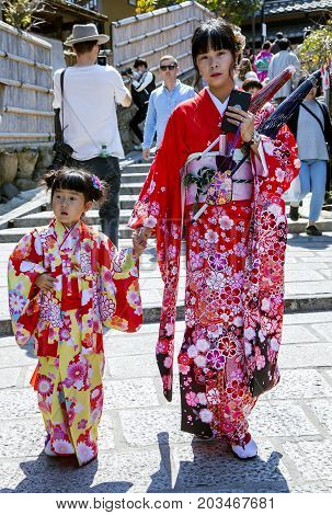 JAPAN, KYOTO, APRIL, 05, 2017 - A young Japanese mother with a little daughter in bright multicolored kimono of Gion district, Kyoto Japan.