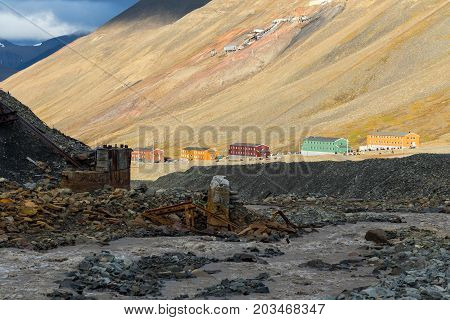 Longyearbyen meltwater river in a glacier moraine and colorful houses of Nybyen in Svalbard in beautiful evening sunlight. Entrance to an abandoned coal mine no. 2 on side of a mountain in background.