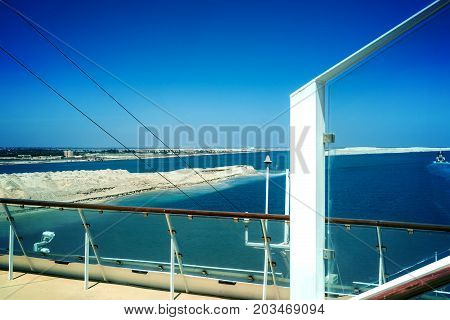 The Suez Canal and the in August 2015 newly opened expansion canal in the foreground rail and windbreak of a cruise ship