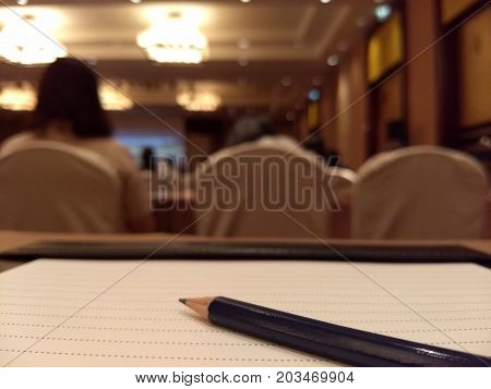 Pencil on peper during meeting in big room training
