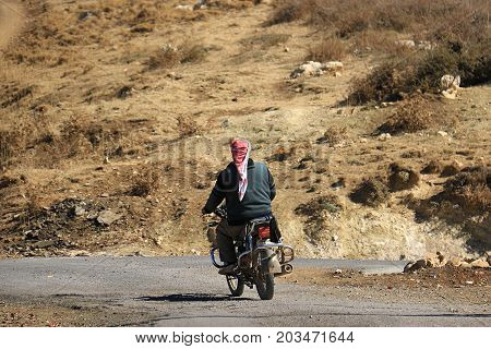 A Syrian refugee riding his motorcycle in the mountains of Lebanon.