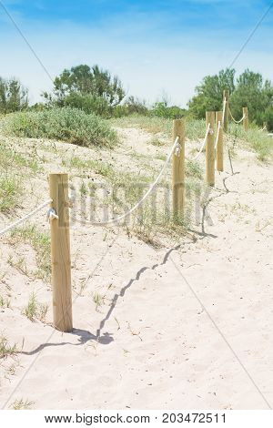 Wood handrail on the sand with rope .