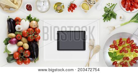 digital tablet above on white cutting board with vegetables saucepan and ingredients on kitchen white wooden worktop copy space top view