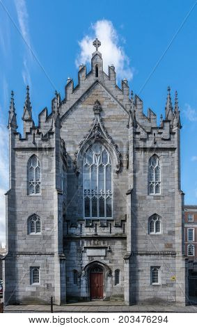 Dublin Ireland - August 7 2017: Entrance facade of original church of The Castle build with dark gray stones under blue sky with white clouds. Frontal view.