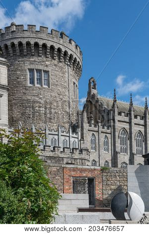 Dublin Ireland - August 7 2017: Thick central gray stone watch tower of The Castle under clear blue sky. Part of castle church on the side. All seen from adjacent Dubh-linn garden.
