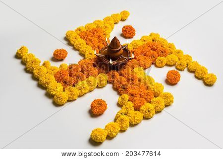 stock photo of hindu auspicious symbol called Swastika or swastik made using marigold flower/zendu/genda phool & diwali diya / clay lamp, Flower rangoli in the shape of Swastika for diwali/pongal/onam