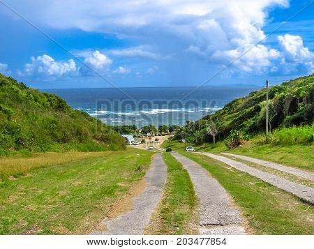 The downhill road to the famous and beautiful beach of Anse Maurice in the north of Grande-Terre in Guadeloupe, West Indies, Caribbean.
