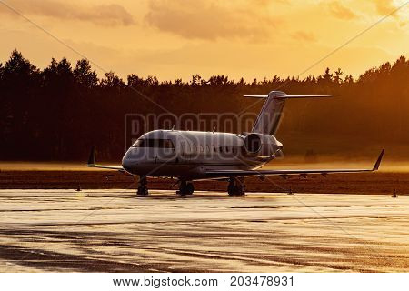 Plane parking at the airport during a foggy sunrise. Modern jet aicraft. Golden time evening.
