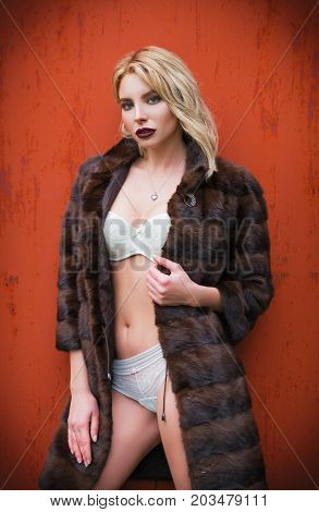 Portrait of sexy young woman in fur coat and underwear