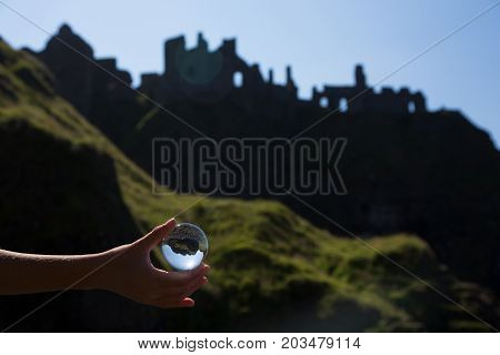 Glass ball in hand, ruins of old irish castle behind, Dunluc