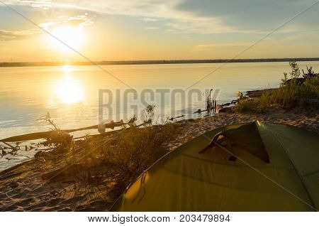 Top tourist tents, standing on the sandy shore of the beach trees, on the background of the bright sunset on the river with reflection in the water.