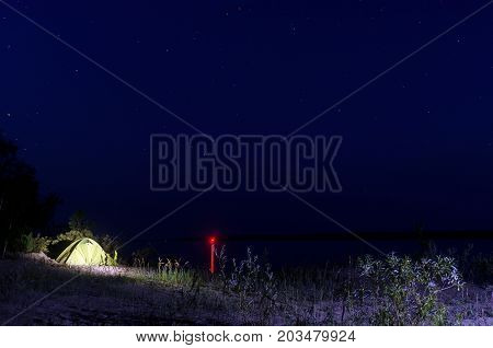 Tourist tent with leaning against a fishing rod, stands on a sandy beach by the river with the lights of the city on the other side of the forest night under the stars, lit by the light of a lantern.