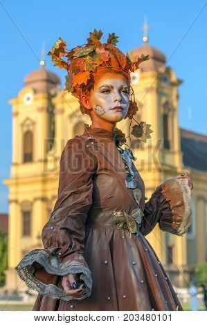 TIMISOARA ROMANIA - SEPTEMBER 8 2017: Living statue of a woman dressed with autumn elements and present on the street inside the CheckART Carnival organized by the City Hall Timisoara. Union Square.