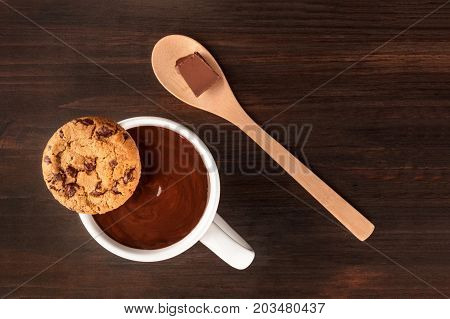 An overhead photo of a chocolate chips cookie on top of a mug of hot chocolate, shot from above on a dark rustic background with a place for text. Selective focus