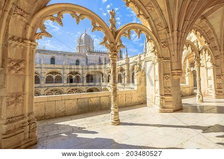 Beautiful reticulated vaulting on courtyard or cloisters of Hieronymites Monastery, Mosteiro dos Jeronimos, famous Lisbon landmark in Belem district and Unesco Heritage. Church dome on background.
