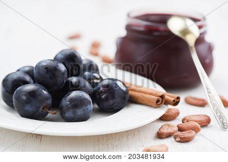 Fresh plums cinnamon sticks raw cocoa beans and homemade plum jam on white background closeup