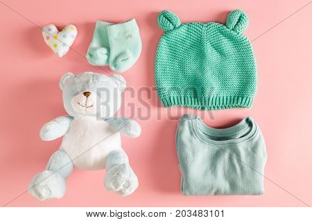 Baby clothes and teddy bear on a pink background