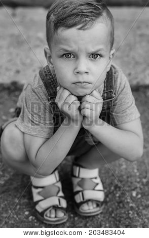 Serious little boy with negative emotions squatting (Black and white)