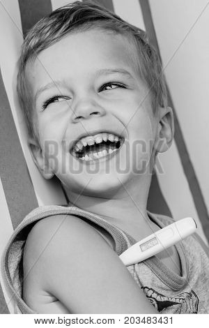 happy laughing little boy sitting measures temperature (Black and white)