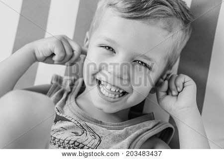 happy little boy covering his ears and laughing (Black and white)