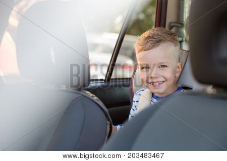 portrait happy toddler boy sitting in the car seat