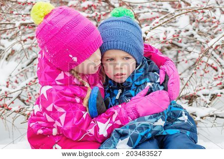 Little children in the snow. Sister hugged and reassured her brother after falling