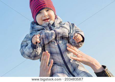 Mother throws up her baby in the sky in nature. winter time