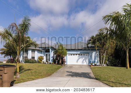 Typical Southwest Florida blue concrete block and stucco home in the countryside with palm trees tropical plants and flowers grass lawn and pine trees. Florida. South Florida single family house
