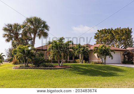 Typical Southwest Florida concrete block and stucco home in the countryside with palm trees tropical plants and flowers grass lawn and pine trees. Florida. South Florida single family house