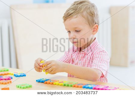 focused cute little child collects puzzles with numbers at the table