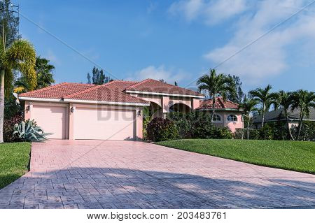 Typical Southwest Florida pink concrete block and stucco home in the countryside with palm trees tropical plants and flowers grass lawn and pine trees. Florida. South Florida single family house