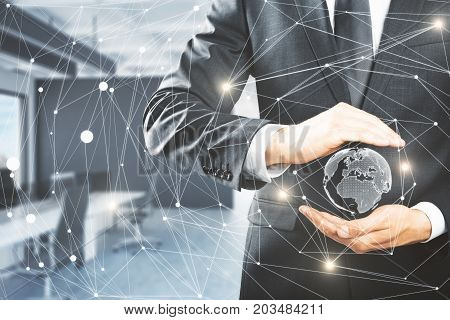 Businessman holding abstract polygonal network with globe on blurry office interior background. International business concept. 3D Rendering