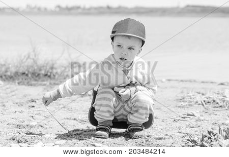 Little boy is sitting on the shore of the lake and playing with stones and sand ( black and white )