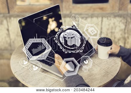 Businessman at small cafe table with coffee cup using laptop and tablet with digital business hologram. Analytics concept